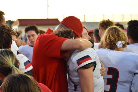 Crimson Cliffs coach Jaron Tate hugs senior Curtis Sweeten after the Mustangs lost to Cedar/