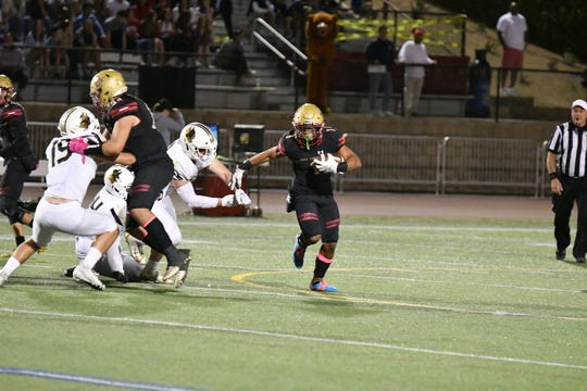 Oaks Christian's Semaj Freeman tries to break free of the Calabasas defense during Friday night's Marmonte League game. The visiting Coyotes won, 30-27.