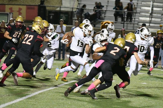 Calabasas High's Jermaine Burton bursts through the Oaks Christian defense during Friday night's Marmonte League game. The Coyotes won, 30-27.