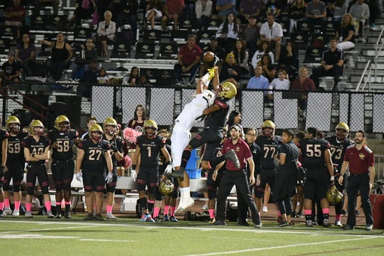 Oaks Christian's Alonzo Fontenette, back, breaks up a pass intended for Calabasas' Johnny Wilson during Friday night's Marmonte League showdown. The visiting Coyotes won, 30-27.