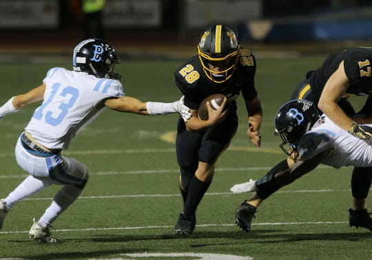 Buena's Andrew Stuart reaches out for Ventura's Dane Kapler slips past Buena's Andrew Stuart (13) during the first quarter of Friday night's rivalry game at Ventura High. The Cougars won, 49-28.