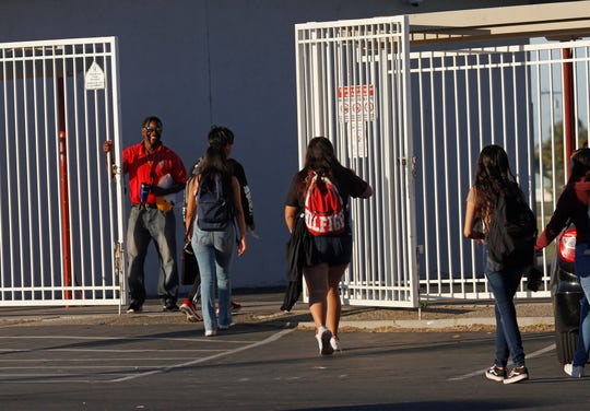 Lead campus supervisor Isaiah Coleman greets students arriving Friday at the back gate at Hueneme High School. The school is one of four in the Oxnard Union High School District that will undergo security upgrades.