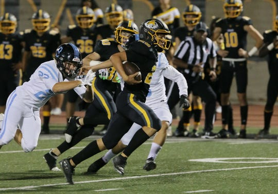 Ventura High's Dane Kapler breaks free from Buena's Tyler Tonoli during the first quarter of Friday night's rivalry game. The host Cougars prevailed, 49-28.