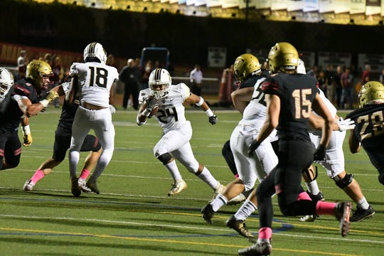 Calabasas High's Myles Coleman has opening to run through during the Coyotes' 30-27 victory over Oaks Christian on Friday night.