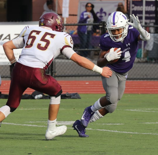 New Rochelle's Gary Phillips carries the ball as Arlington's Connor Price closes in during their Section One Class AA Quarterfinal football game in New Rochelle, Oct 26, 2019.