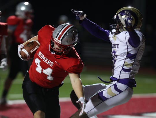 Somers' Jack Kaiser runs for a touchdown past Clarkstown North's Mikenly Pierre during their Class A quarterfinal at Somers, Oct. 25, 2019. Somers won 35-0.