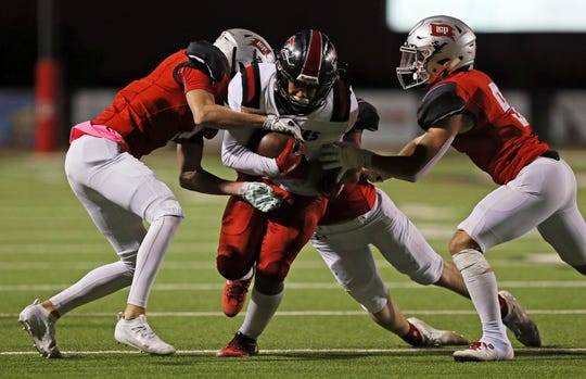 Wichita Falls' Khelyn Sapp (5) is tackled by a group of Lubbock-Cooper Pirates during the game against Wichita Falls, Friday, Oct. 25, 2019, at Pirate Stadium at First United Park in Lubbock, Texas. [Sam Grenadier/A-J Media]