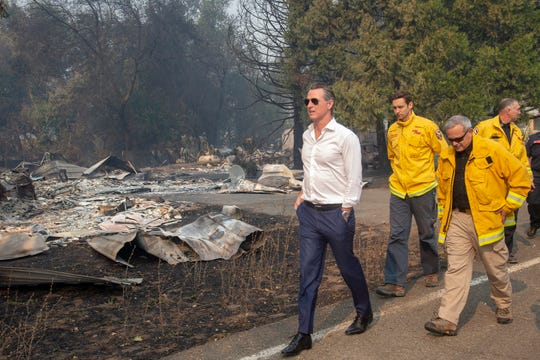 California Gov. Gavin Newsom, left, tours a home destroyed by the Kincade fire on Friday, Oct. 25, 2019, in Geyserville, Calif.