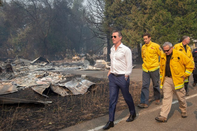 California Gov. Gavin Newsom, left, tours a home destroyed by the Kincade fire on Friday, Oct. 25, 2019, in Geyserville, Calif. Newsom declared a state of emergency Friday as wildfires scorch both ends of the state from Sonoma to Los Angeles.