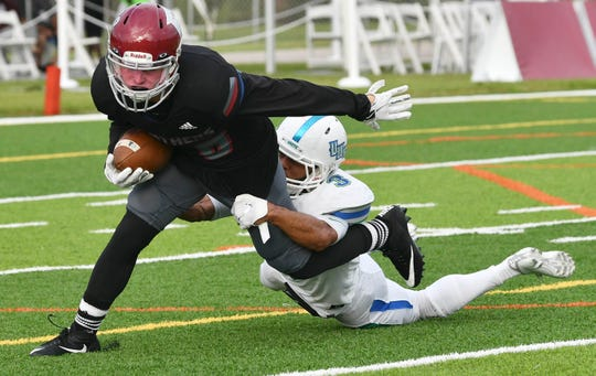 Max Erdman of Florida Tech is brought down by West Florida's Marcus Clayton during a game in Melbourne.