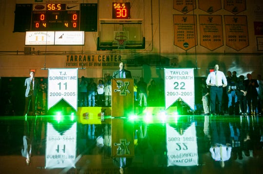 T.J. Sorrentine, left, and Taylor Coppenrath, right, listen to UVM athletic director Jeff Schulman during Saturday's special ceremony to retire the jerseys  of Sorrentine (No. 11) and Coppenrath (No. 22)/