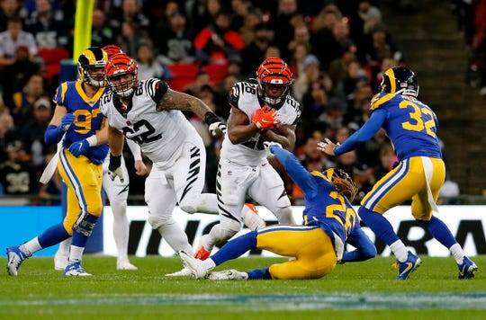 Cincinnati Bengals running back Joe Mixon (28) runs through an opening in the second quarter of the NFL Week 8 game between the Los Angeles Rams and the Cincinnati Bengals at Wembley Stadium in Wembley, London, on Sunday, Oct. 27, 2019.