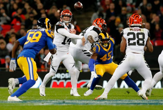 Cincinnati Bengals quarterback Andy Dalton (14) throws a short pass over the middle to running back Joe Mixon (28) in the second quarter of the NFL Week 8 game between the Los Angeles Rams and the Cincinnati Bengals at Wembley Stadium in Wembley, London, on Sunday, Oct. 27, 2019.