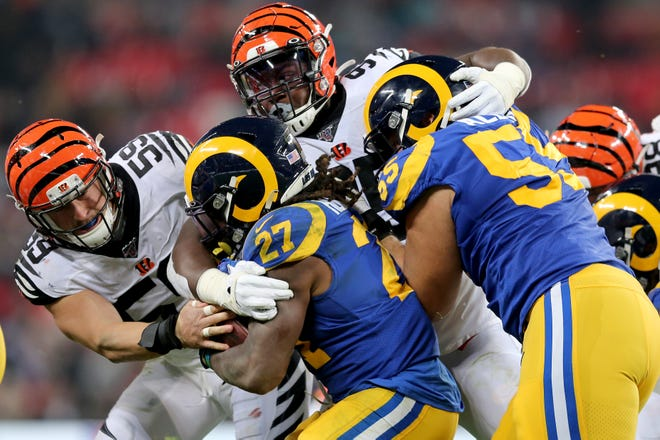 Cincinnati Bengals outside linebacker Nick Vigil (59) and Cincinnati Bengals defensive tackle Renell Wren (95) combine to tackle Los Angeles Rams running back Darrell Henderson (27) in the fourth quarter of a Week 8 NFL game, Sunday, Oct. 27, 2019, at Wembley Stadium in London, England. The Los Angeles Rams won 24-10.