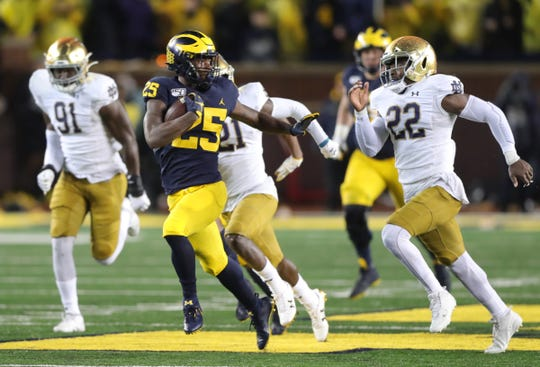 Michigan Wolverines running back Hassan Haskins runs by Notre Dame defenders during the second half Saturday, Oct. 26, 2019 at Michigan Stadium.