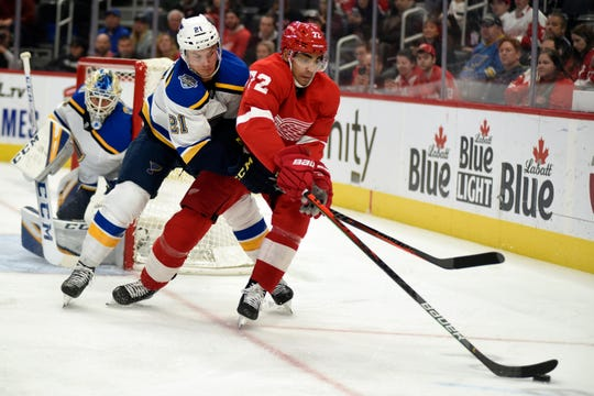 Detroit Red Wings left wing Andreas Athanasiou moves the puck away from St. Louis Blues center Tyler Bozak in the second period Sunday, Oct. 27, 2019.