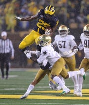 Hassan Haskins goes airborne against Notre Dame during the first half Saturday.