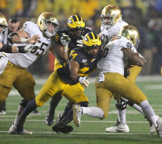 Michigan Wolverines linebacker Cameron McGrone tackles Notre Dame running back Tony Jones Jr. on Saturday, Oct. 26, 2019 at Michigan Stadium.