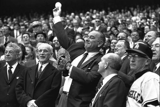 FILE - In this April 13, 1964, file photo, President Lyndon Johnson throws out the first pitch to open the American League baseball season in Washington. The first pitch ceremony preceded the opening game between the Los Angeles Angels and the Washington Senators. At left is House Speaker John McCormack of Massachusetts.
