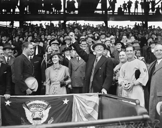 FILE - In this April 14, 1936, file photo, President Franklin D. Roosevelt prepares to throw the traditional first pitch in Washington, opening the baseball season with a game between the Senators and the Yankees at Griffith Stadium. From left: Roosevelt's son Elliott; Betsy Cushing Roosevelt, wife of FDR's eldest son, James; the president; Yankees manager Joe McCarthy; and Senators manager Bucky Harris.