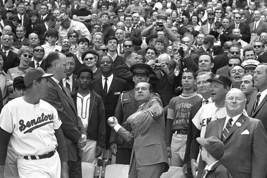 FILE - In this April 7, 1969, file photo, President Richard M. Nixon throws out the ceremonial first pitch in Washington as Baseball Commissioner Bowie Kuhn, second from left, and Washington Senators manager Ted Williams, far left, watch.