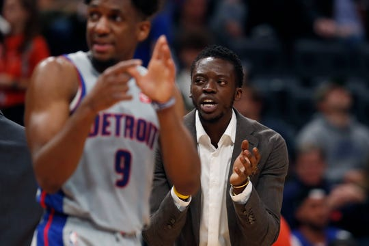 Detroit Pistons guard Reggie Jackson, right, cheers his team on earlier this season.