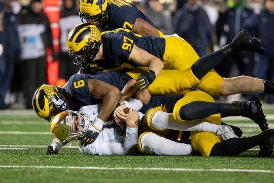 Notre Dame quarterback Phil Jurkovec is piled on by linebacker Josh Uche (6) defensive lineman Aidan Hutchinson (97) and linebacker Khaleke Hudson (7) in the fourth quarter.
