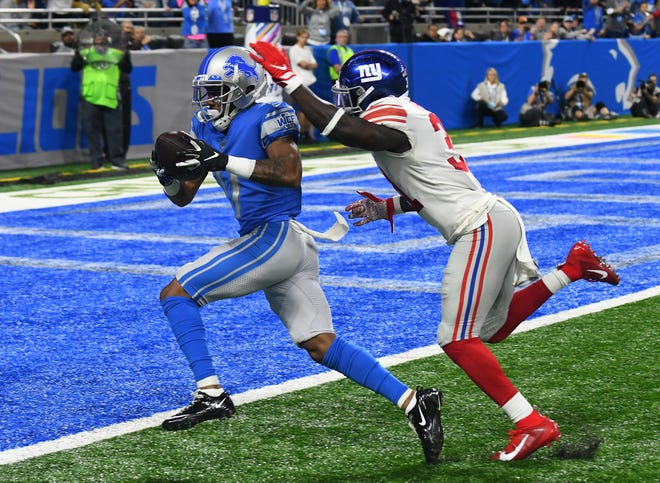 Lions' Marvin Hall has plenty of room in front of Giants' Michael Thomas and hauls in a 49-yard touchdown reception in the first quarter on Sunday.