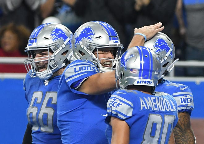 Lions quarterback Matthew Stafford with Joe Dahl and teammates celebrate Marvin Jones Jr. touchdown reception in the fourth quarter.