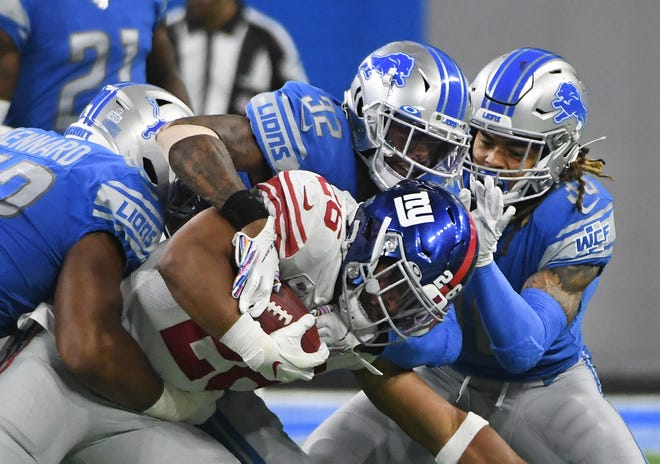 Lions' Devon Kennard, Tavon Wilson and Mike Ford bring down Giants' Saquon Barkley in the third quarter.