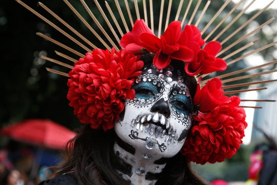 A woman dressed as Catrinas poses for a photo as she joins a parade on Mexico City's iconic Reforma avenue during celebrations for the Day of the Dead in Mexico, Saturday, Oct. 26, 2019.
