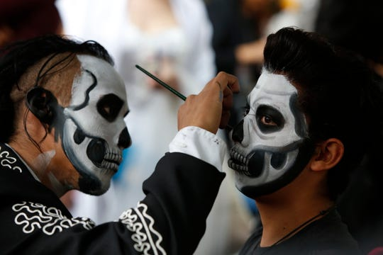 Ulises Armendariz, left, paints a customers face like a skull before the Catrinas parade down Mexico City's iconic Reforma avenue during Day of the Dead celebrations, Saturday, Oct. 26, 2019.