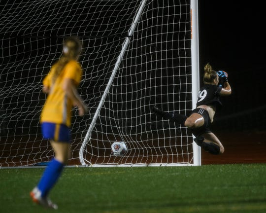 A shot made by Carmel's Olivia Fray (20) blasts past Castle goalkeeper Kassidy Elkin (99) during the second half of the IHSAA Class 3A semistate matchup at Bundrant Stadium in Evansville, Ind., Saturday, Oct. 26, 2019. The Greyhounds defeated the Knights, 1-0, to advance to the Class 3A state championship.