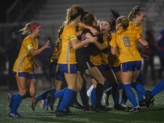 Carmel's Olivia Fray (20) is embraced by her team after making the first and only goal of the game during the second half of the IHSAA Class 3A semistate matchup against the Castle Knights at Bundrant Stadium in Evansville, Ind., Saturday, Oct. 26, 2019. The Greyhounds will advance to the Class 3A state championship.
