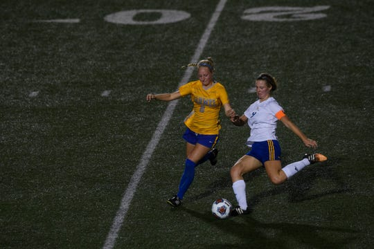 Castle's Daelyn Quinn (9) kicks the ball away from Carmel's Brooke Bailey (8) during the first half of the IHSAA Class 3A semistate matchup at Bundrant Stadium in Evansville, Ind., Saturday, Oct. 26, 2019. The Knights fell to the Greyhounds, 1-0.