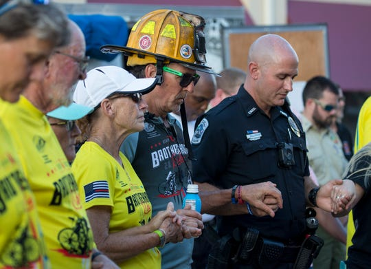 Georgia Wood, left, Jack Bills, center, and Officer Steve Pellizzaro pray together during the invocation at the closing ceremony for the Brotherhood Ride in Fort Myers on Saturday, Oct. 26, 2019. Wood was on the support team and Bills was one of the riders who cycled more than 600 miles in seven days to support fallen officers and firefighters in Florida.