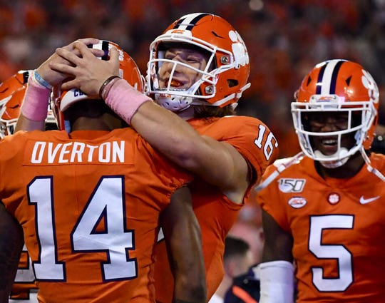 Clemson quarterback Trevor Lawrence (16) celebrates with Diondre Overton (14) after a touchdown against Boston College on Saturday, Oct. 26, 2019.