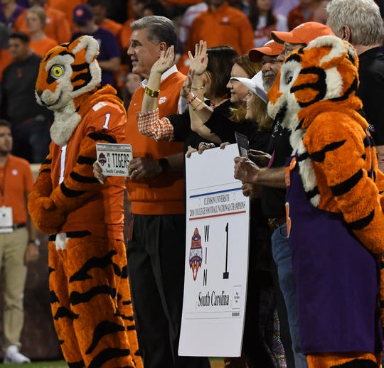 The Tiger and Dan Radakovich hold a National Championship license plate sample before the game at Memorial Stadium with Boston College in Clemson, South Carolina Saturday, October 26, 2019.