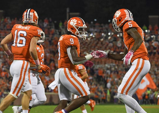 Clemson running back Travis Etienne (9) is congratulated by wide receiver Tee Higgins (5) after scoring during the first quarter at Memorial Stadium with Boston College in Clemson, South Carolina Saturday, October 26, 2019.