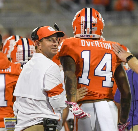 Clemson Head Coach Dabo Swinney looks back after greeting wide receiver Diondre Overton (14) following his third touchdown catch during the fourth quarter at Memorial Stadium before the game with Boston College in Clemson, South Carolina Saturday, October 26, 2019.