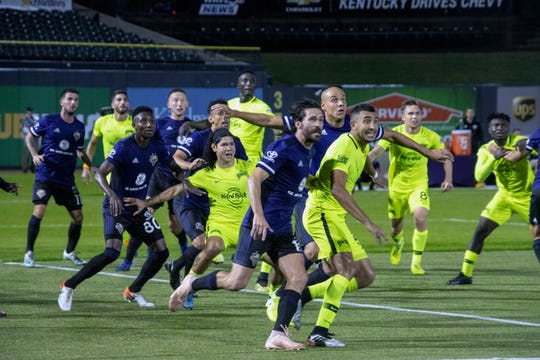 Louisville City FC players run alongside the Tampa Bay Rowdies during Saturday's game.