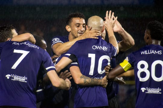 Louisville City FC players, including Magnus Rasmussen (7), Paco Craig (facing the camera), Brian Ownby (10) and Speedy Williams (80) celebrate after a goal Saturday.