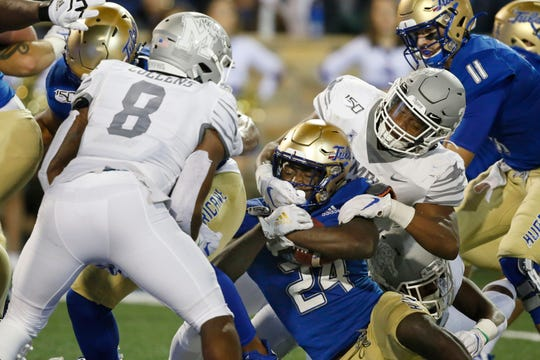 Tulsa running back Corey Taylor II (24) fights his way past Memphis defenders Xavier Cullens (8) and Tim Hart, right, into the end zone to score in the first half of an NCAA college football game in Tulsa, Okla., Saturday, Oct. 26, 2019.