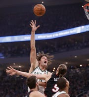 Robin Lopez of the Bucks throws up a hook shot over the Heat's Kelly Olynyk.
