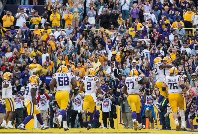 LSU quarterback Joe Burrow (9) celebrates with his team after running in for a touchdown at Tiger Stadium in Baton Rouge, La., on Saturday, Oct. 26, 2019. LSU defeated Auburn 23-20.