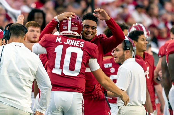 Alabama quarterback Tua Tagovailoa,  hugs fellow quarterback Mac Jones (10) during the Crimson Tide's game against Arkansas on Oct. 26, 2019.