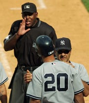 In this July 3, 2004, file photo, home plate umpire Chuck Meriwether, left, talks to New York Yankees' Jorge Posada (20) as manager Joe Torre gets between them after Posada was called out on strikes with the bases loaded to end the ninth inning against the Mets at Shea Stadium.