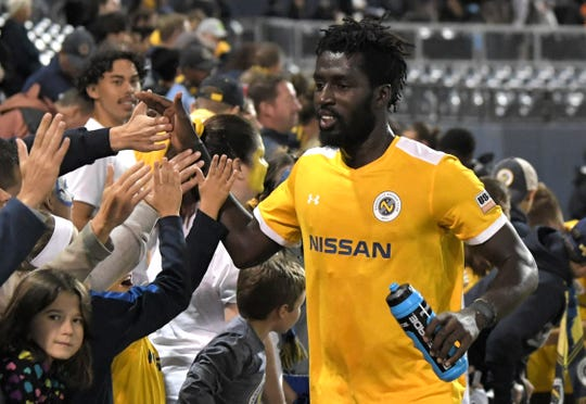 Nashville SC's Derrick Jones (4)  high fives fans after winning a Eastern Conference Quarterfinal match at First Tennessee Park in Nashville on Saturday, Oct. 26, 2019.