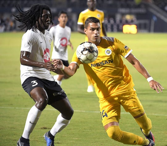 Nashville SC forward Daniel Rios (14) runs the ball down against Charleston Battery defender Kyle Nelson (3) during a playoff match Oct. 26. Nashville next faces Indy Eleven in the Eastern Conference semifinals.