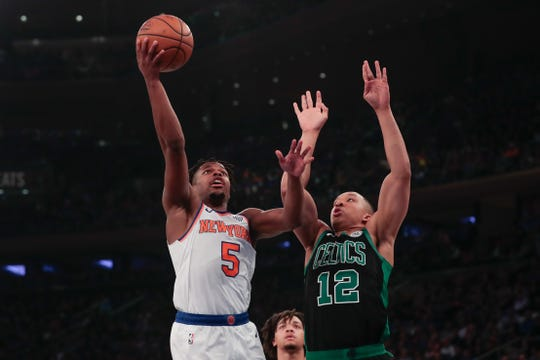 Oct 26, 2019; New York, NY, USA; New York Knicks guard Dennis Smith Jr. (5) shoots the ball as Boston Celtics forward Grant Williams (12) defends during the first half at Madison Square Garden.